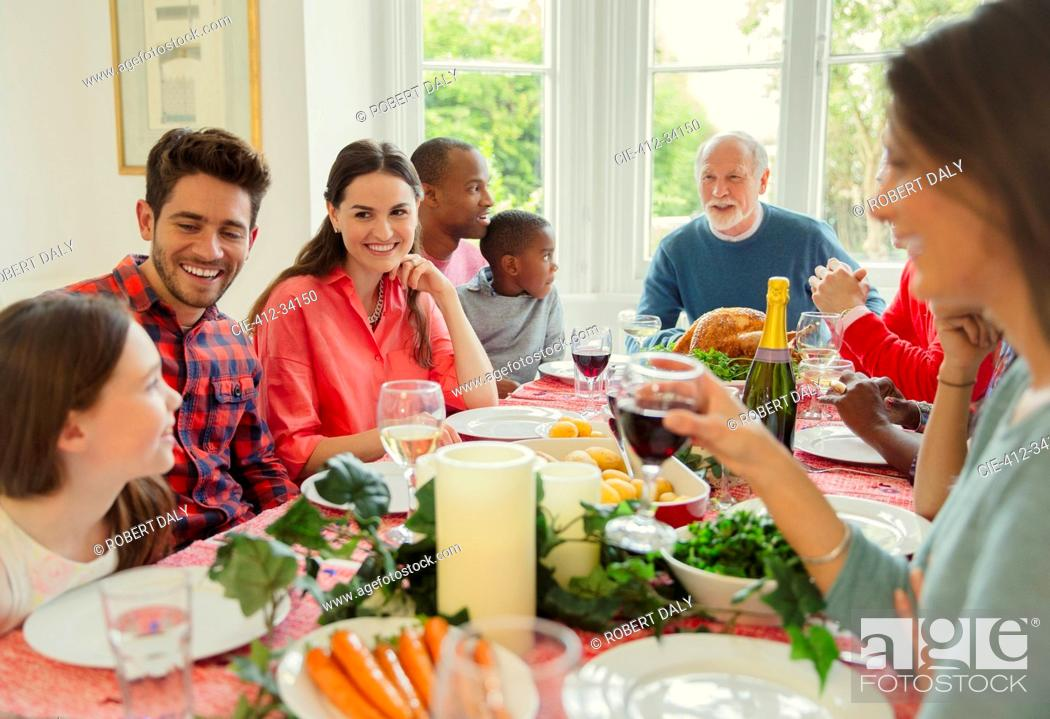 Stock Photo: Multi-ethnic multi-generation family enjoying Christmas dinner at table.