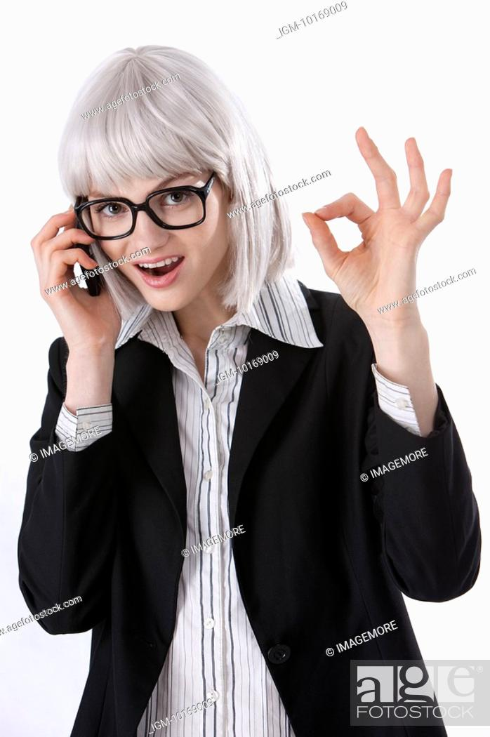 Stock Photo: Young businesswoman giving ok sign, talking on the phone.