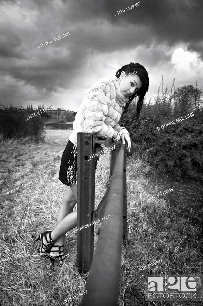 Stock Photo: Female model leaning on rail.