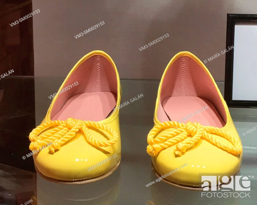 Stock Photo: Yellow ballet flats in a shop window.