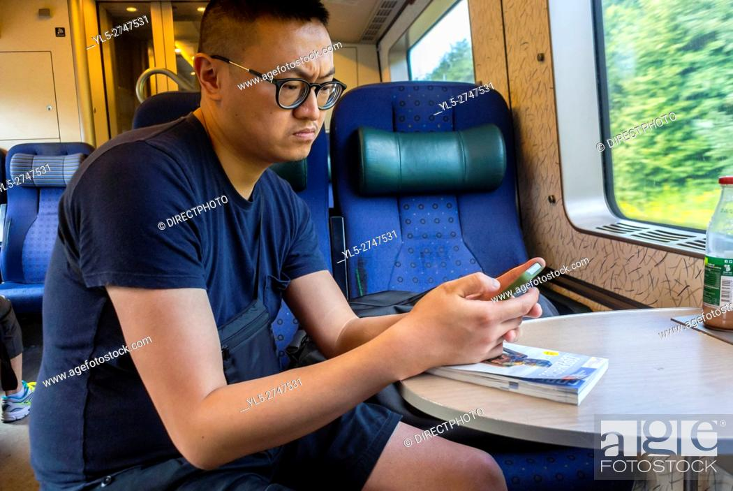 Stock Photo: Copenhagen, Denmark, Chinese Tourist Looking at Smart Phone, Inside Train.
