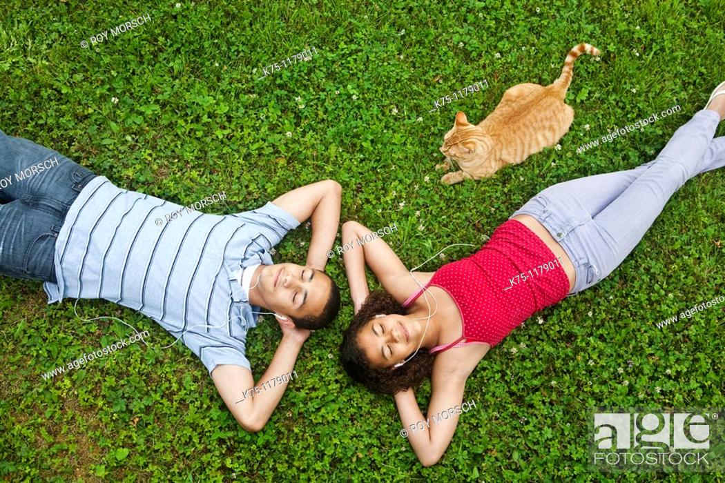 Stock Photo: teenagers listening to music and relaxing with pet cat.