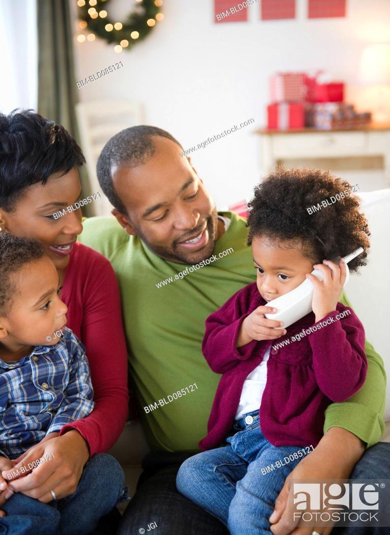 Black family watching girl talking on telephone, Stock Photo