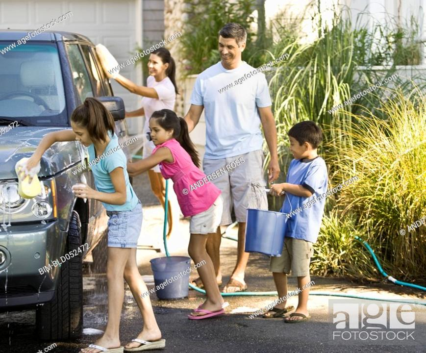 Stock Photo: Hispanic family washing car.