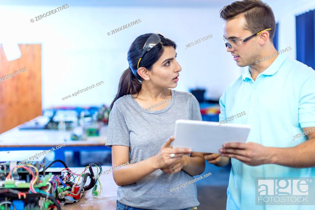 Stock Photo: Technicians in workshop having a discussion.