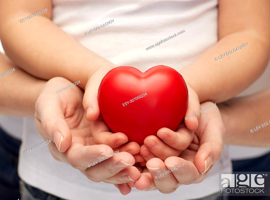 Stock Photo: people, charity, family and advertisement concept - close up of woman and girl holding red heart shape in cupped hands.