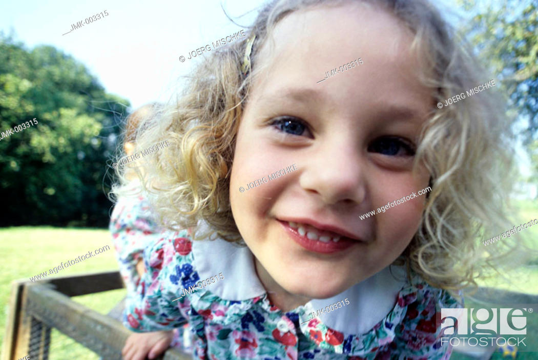 Stock Photo: A little girl, 1-5 years old, in the garden in summer.