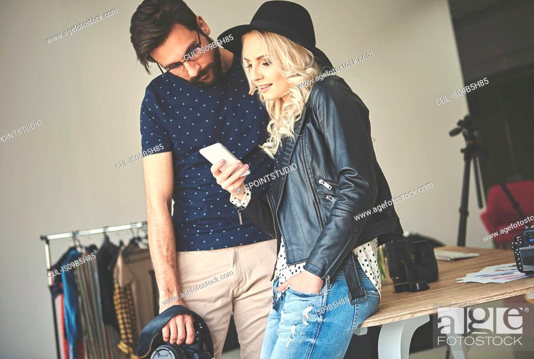 Stock Photo: Photographer and stylist looking at smartphone in photography studio.