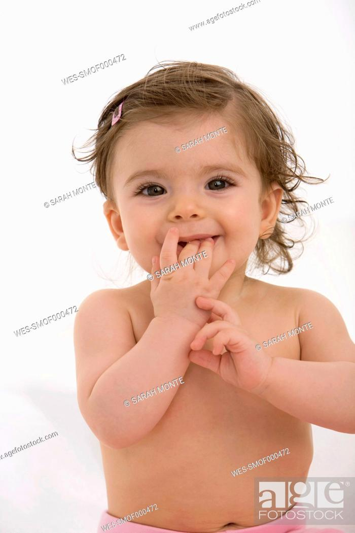Stock Photo: Baby girl with finger in mouth, portrait.