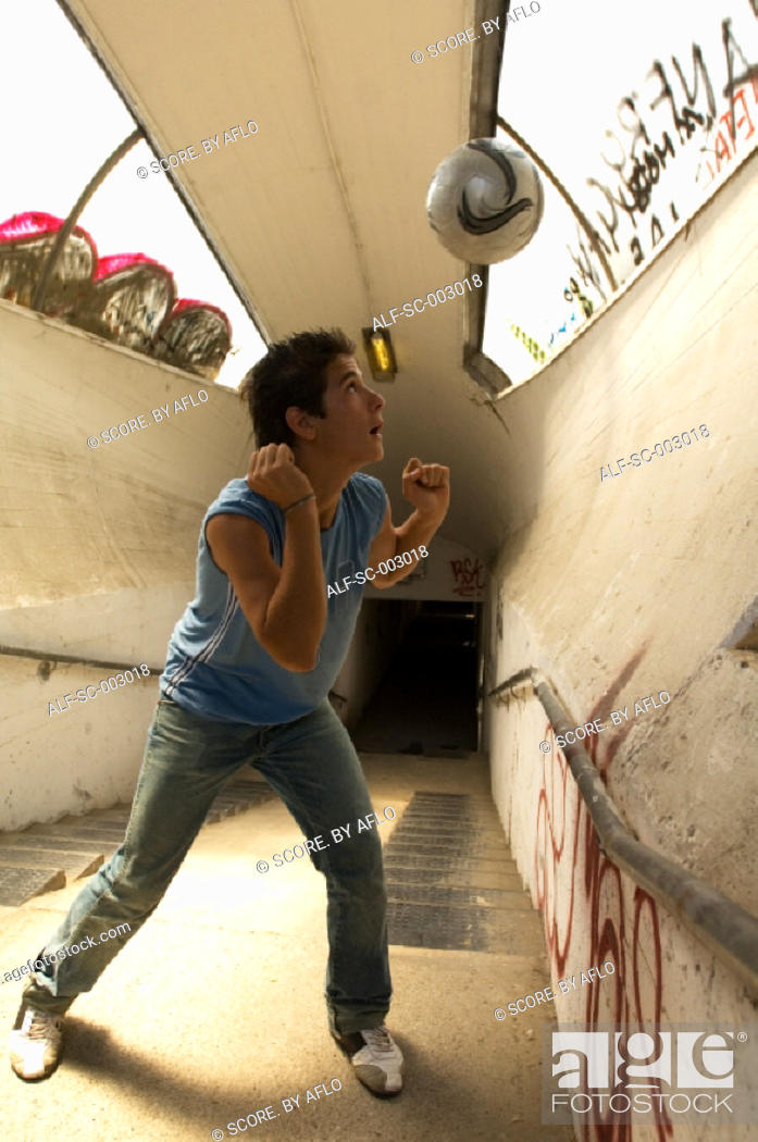 Stock Photo: Teenage boy heading ball in underpass.