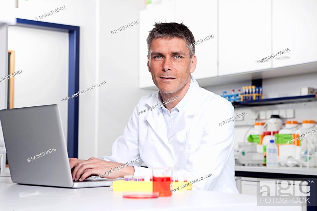 Stock Photo: Germany, Bavaria, Munich, Scientist with laptop in laboratory, portrait.