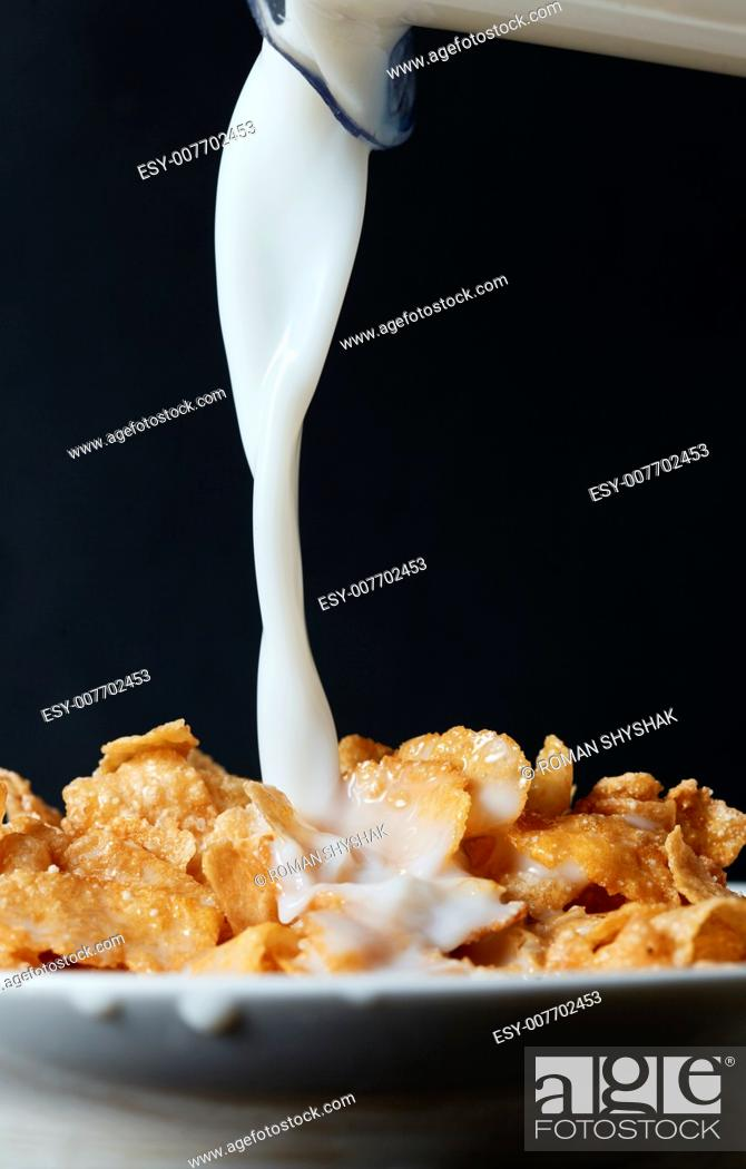 Stock Photo: Corn flakes breakfast with milk being poured over it.