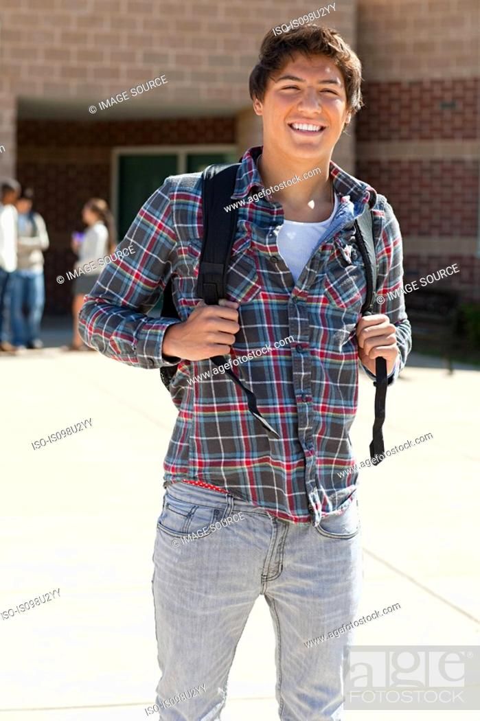 Stock Photo: Male high school student outside school building.