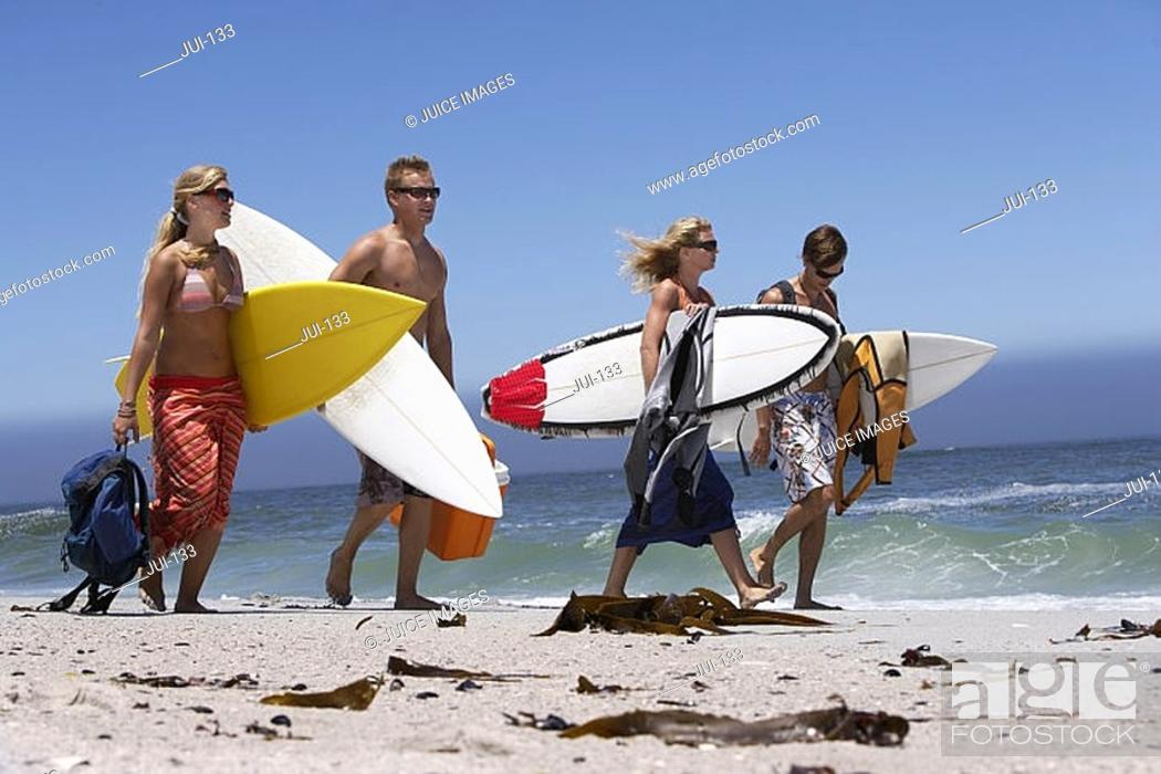 Stock Photo: Four young friends walking on beach, carrying surfboards underarm, sea in background.