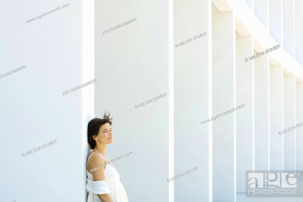 Stock Photo: Woman leaning against column, eyes closed, hair tousled by breeze.