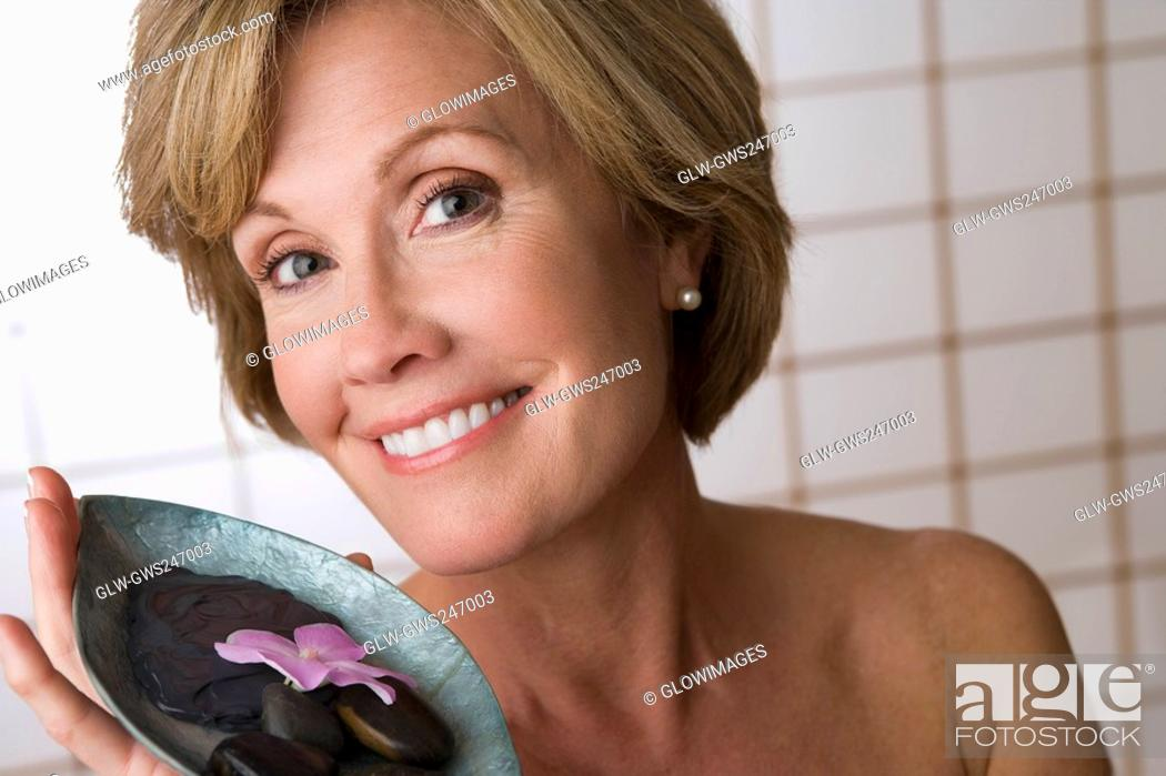 Stock Photo: Portrait of a mature woman holding a bowl of pebbles and a flower.
