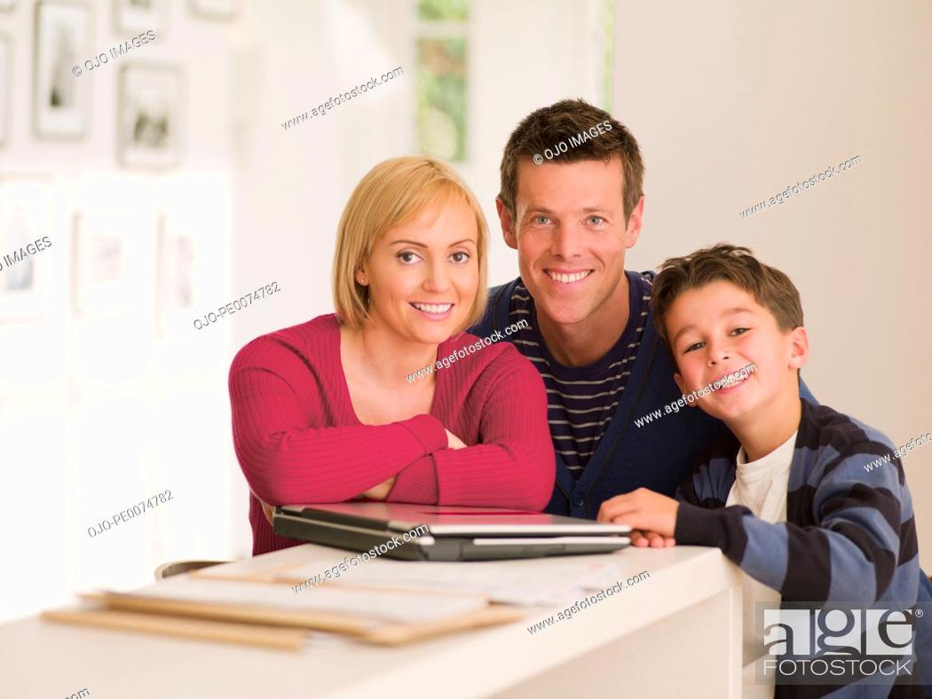 Stock Photo: Smiling family standing near laptop.