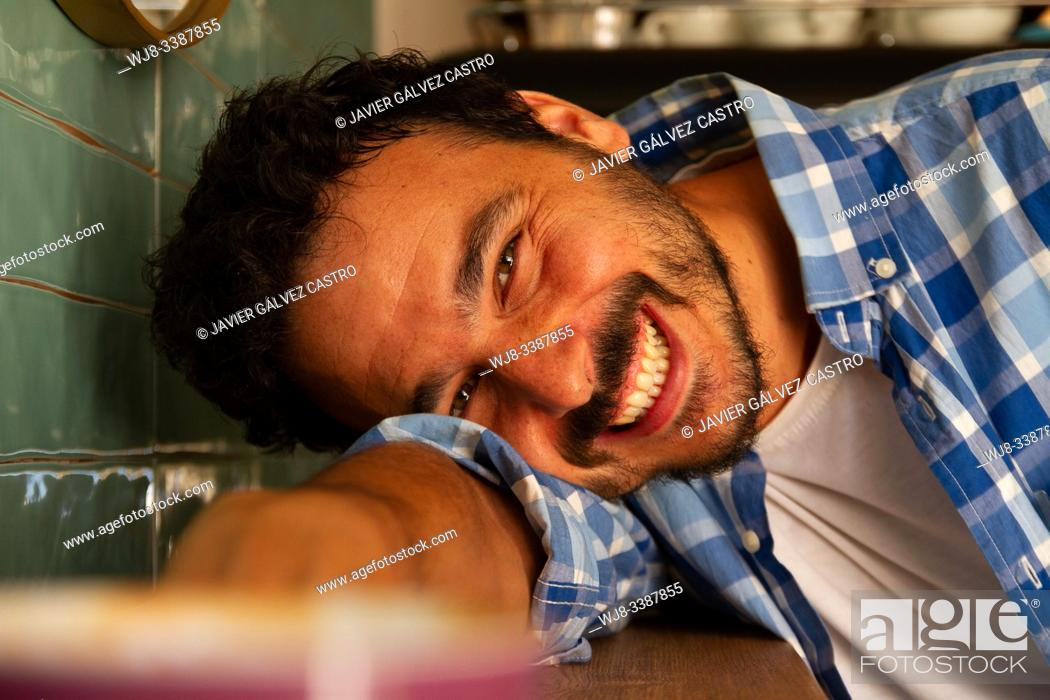 Stock Photo: Young man leaning on a coffee shop table smiling.