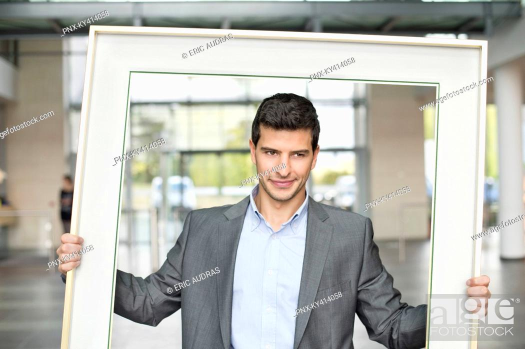 Stock Photo: Close-up of a businessman holding a frame in an office lobby.