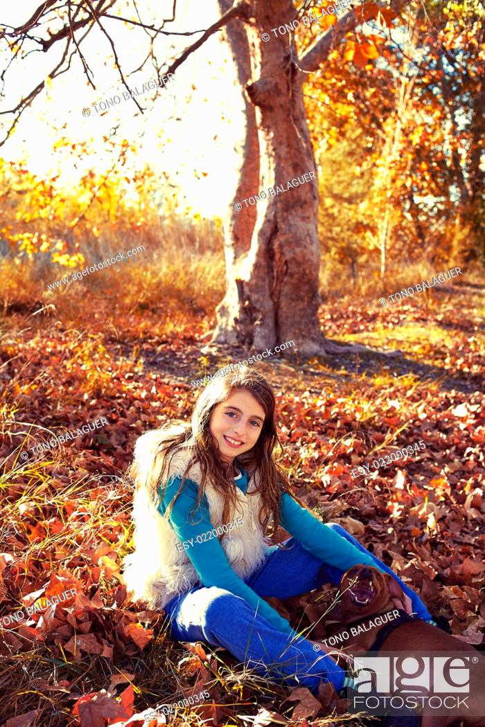 Stock Photo: Autumn kid girl with pet dog relaxed in fall forest in Parc de Turia Valencia Spain.