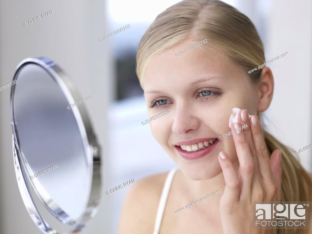 Stock Photo: Woman applying lotion or cream to face in mirror.