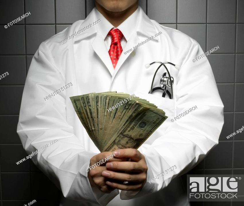 Stock Photo: Doctor Holding US Dollars.