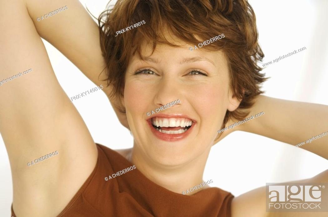 Stock Photo: Portrait of young smiling woman, hands behind head.