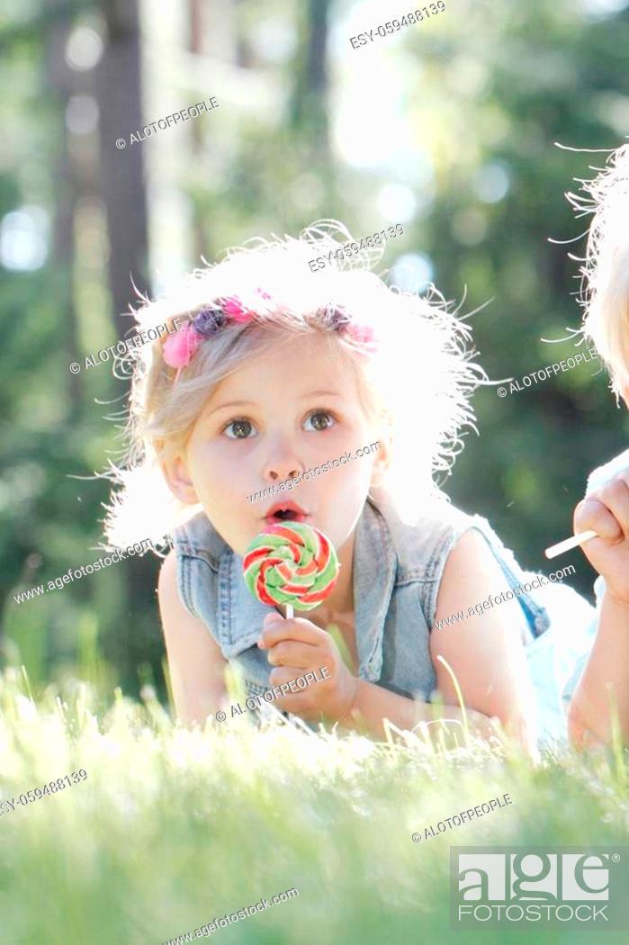 Photo de stock: Group of happy children eating lollipops outdoors in summer park.