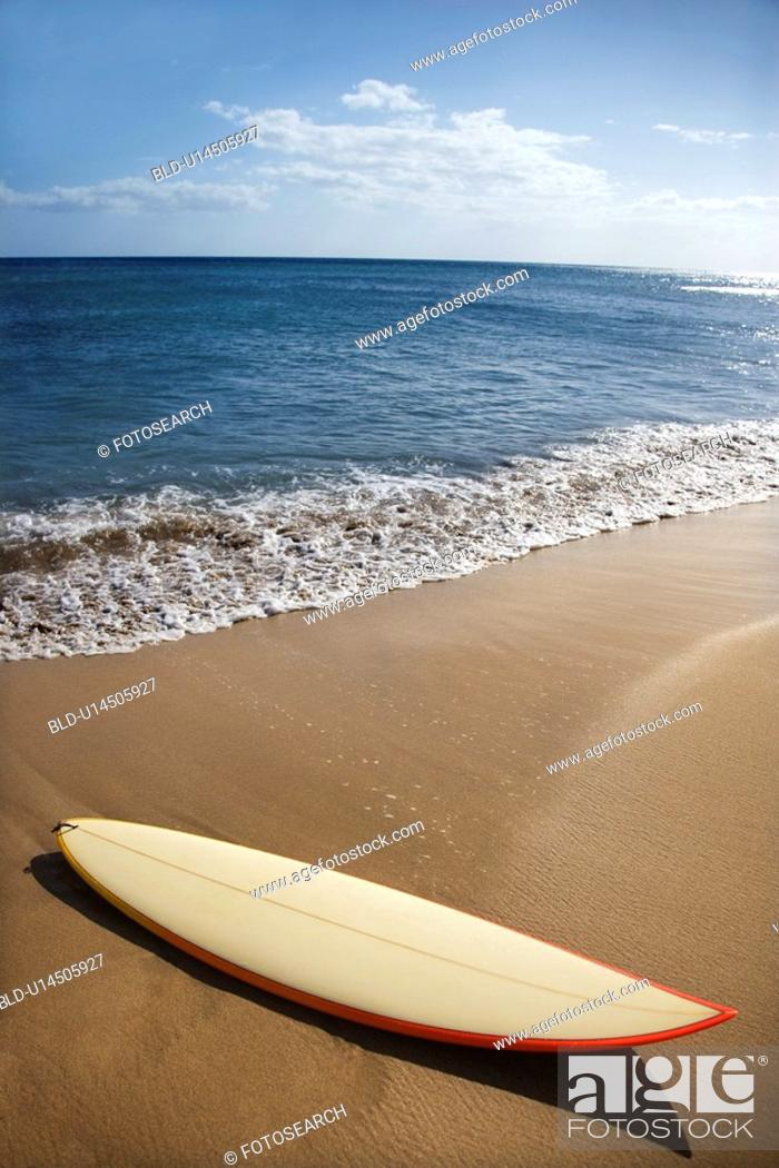 Stock Photo: Surfboard on sandy beach with ocean in background.