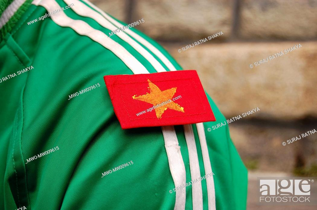 Stock Photo: The symbol of YCL Young Communist League carried by a young Maoist activist in Manang, Nepal April 25, 2007.