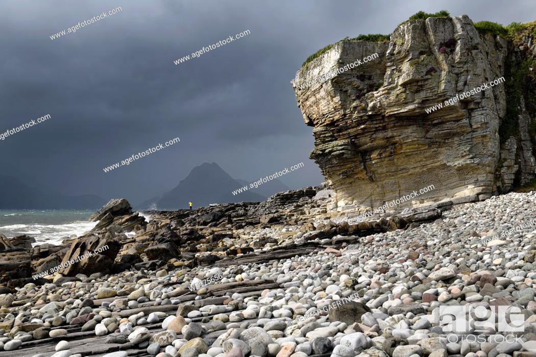 Stock Photo: Tourist on Elgol beach at Port na Cullaidh with Red Cuillin Mountains under clouds on Loch Scavaig Scottish Highlands Isle of Skye Scotland.