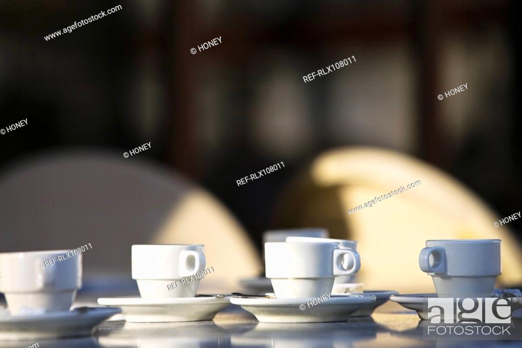 Stock Photo: Several white coffee cups and saucers on cafe table, Paris, France.
