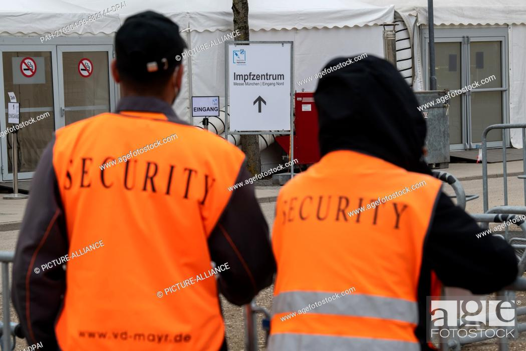 """Stock Photo: 04 March 2021, Bavaria, Munich: A sign on the grounds of the Munich Trade Fair Centre displays the word """"""""Impfzentrum"""""""" (Vaccination Centre) at the entrance."""