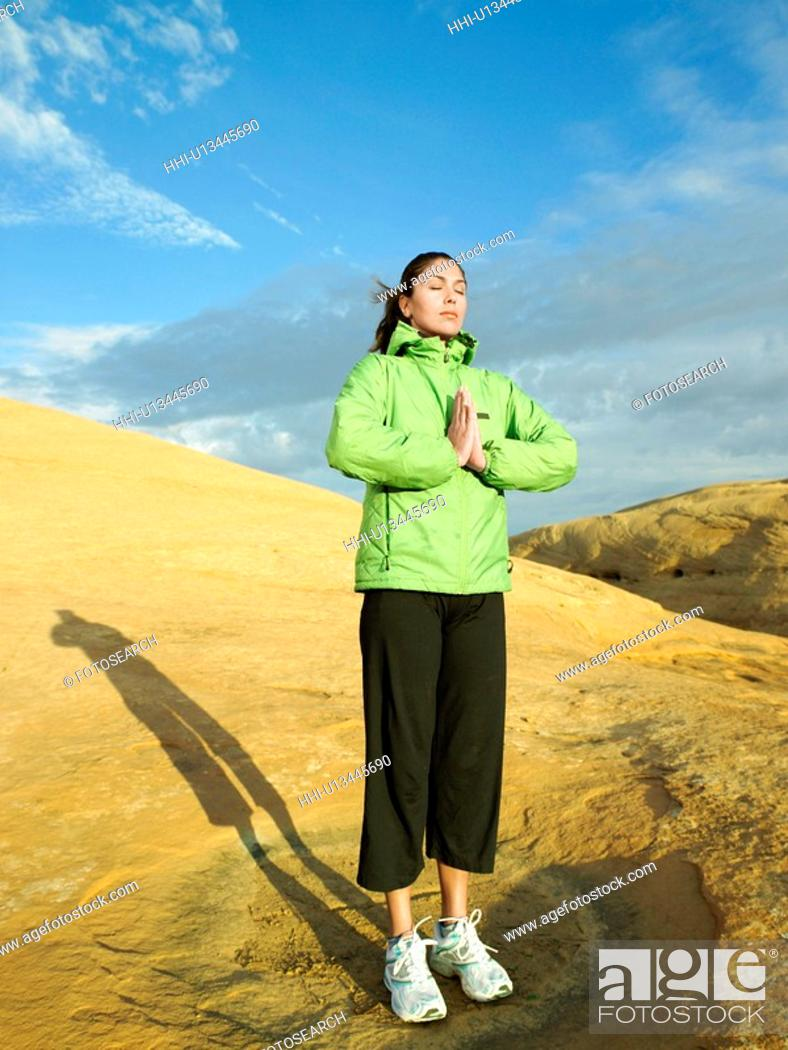 Stock Photo: Woman meditating on rocky hill.