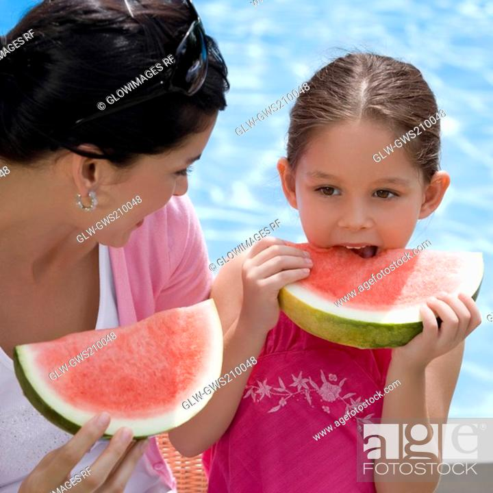 Stock Photo: Close-up of a young woman and her daughter eating watermelon.