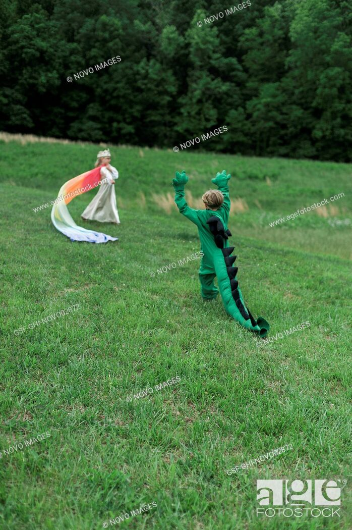 Imagen: Young Boy in Dragon Costume Playing with Young Girl in Princess Costume in Grassy Field.