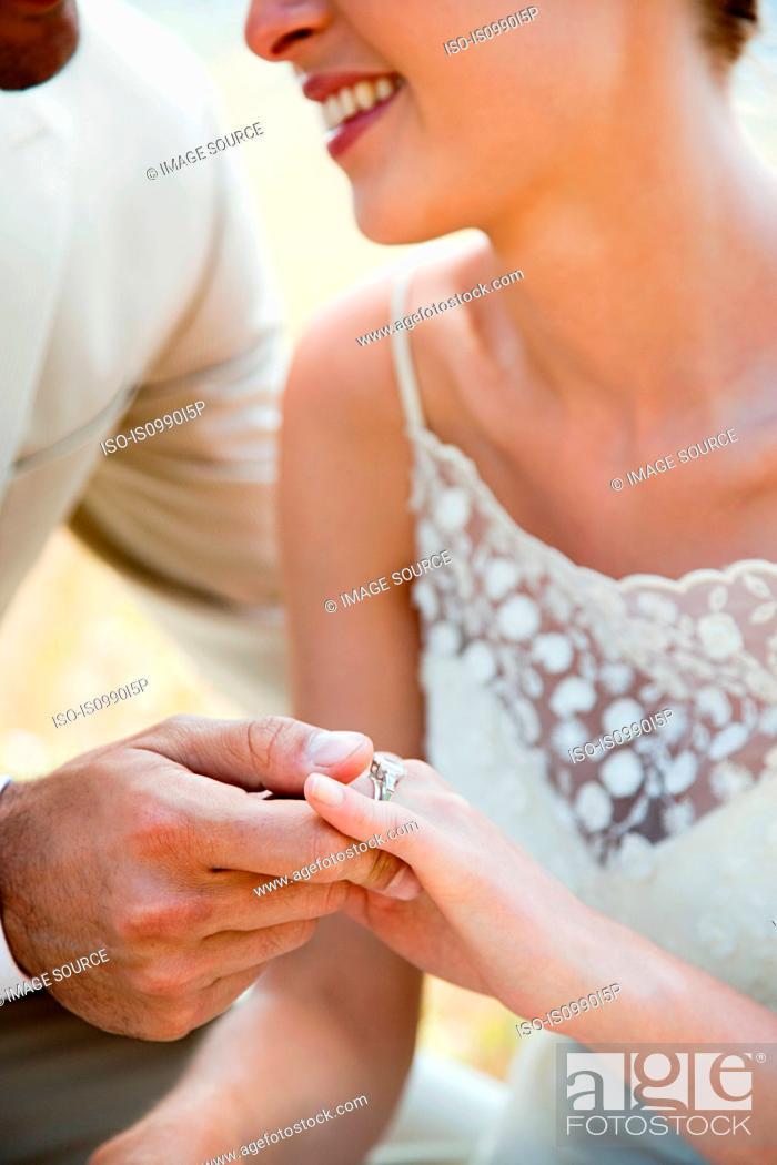 Stock Photo: Newlyweds looking at wedding ring, close up.