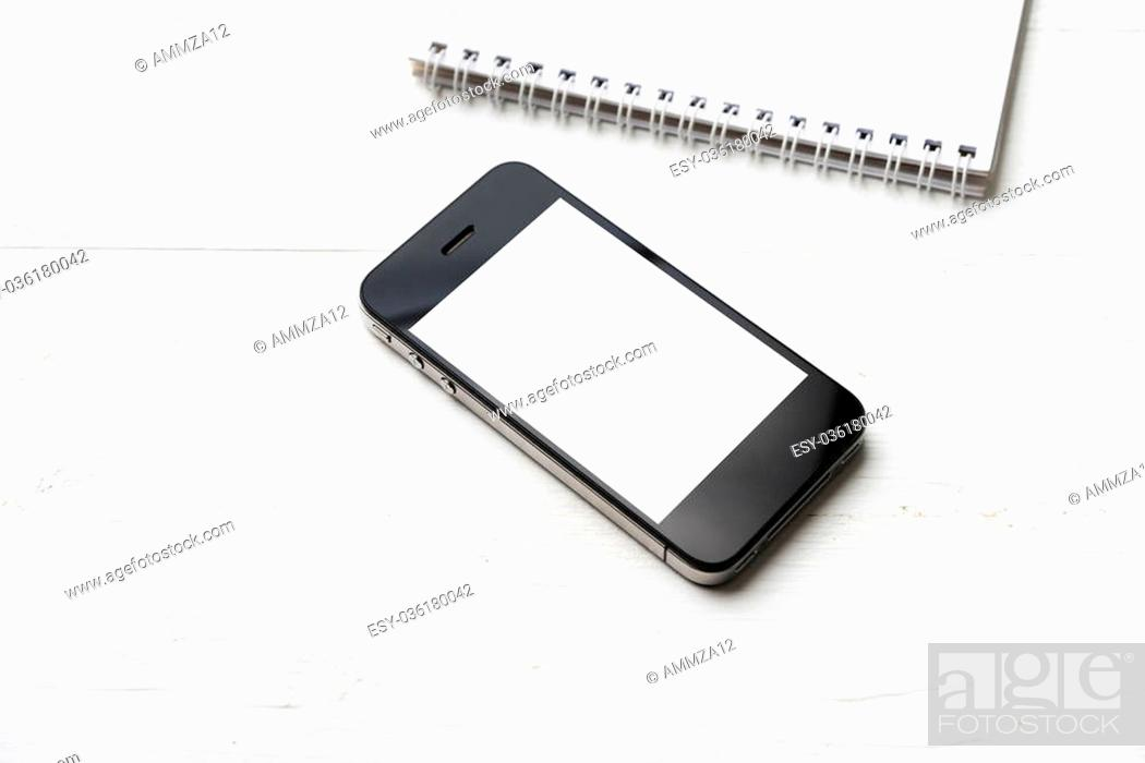 Stock Photo: cellphone with notepad over white table.