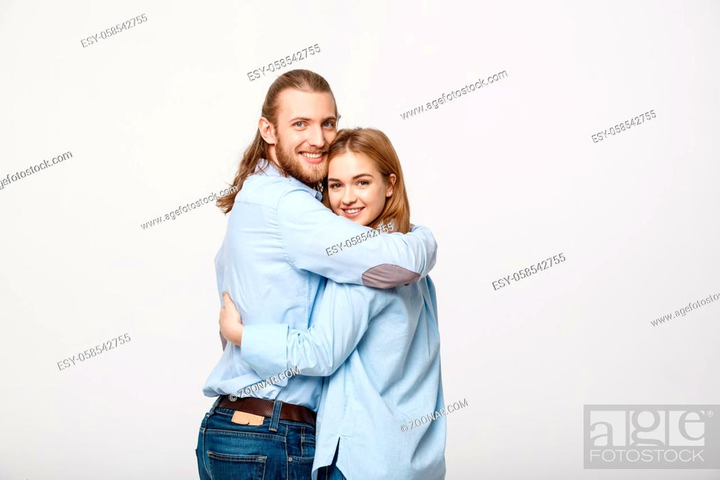 Stock Photo: Portrait of cheerful young couple standing and hugging each other on isolated white background.
