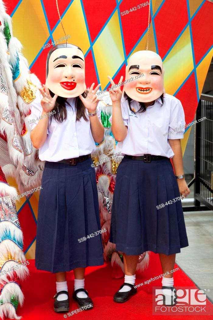 School girls wearing Chinese Lucky God masks, Bangkok