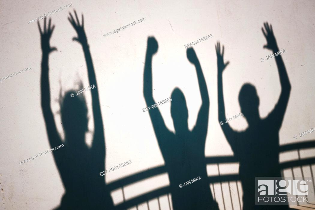 Imagen: Creative photo of ecstatic people shadows on white wall.