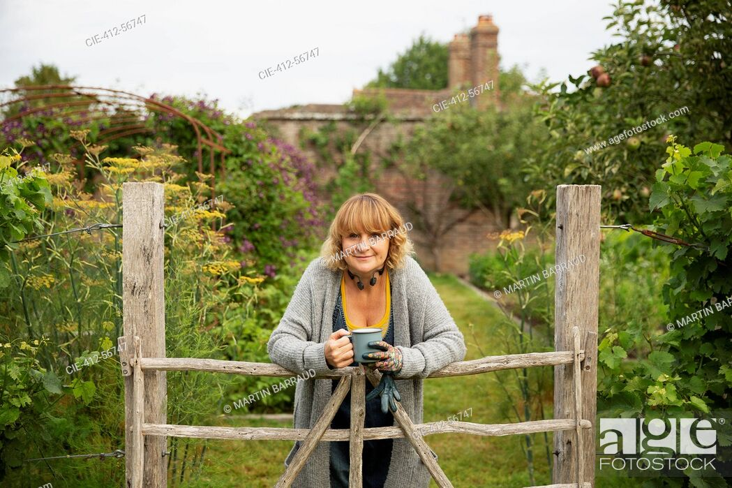 Stock Photo: Portrait confident woman with tea at gate in idyllic cottage garden.