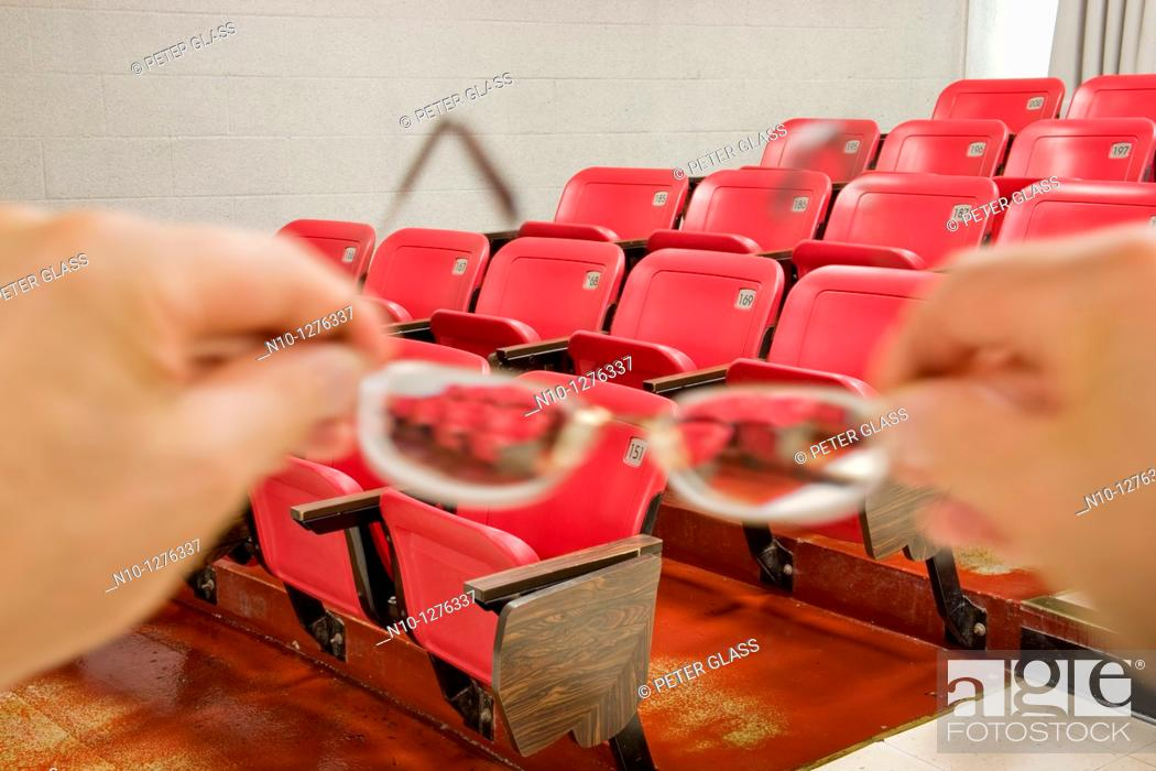 Stock Photo: Man holding his glasses in an auditorium.