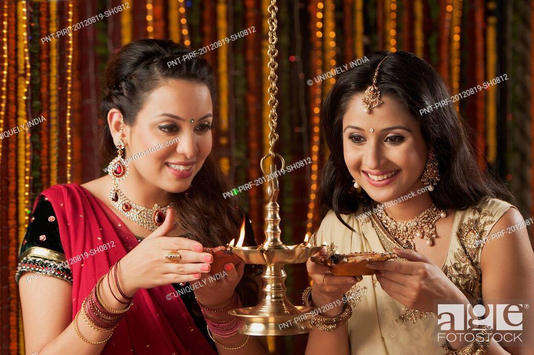 Stock Photo: Female friends burning oil lamps on Diwali.