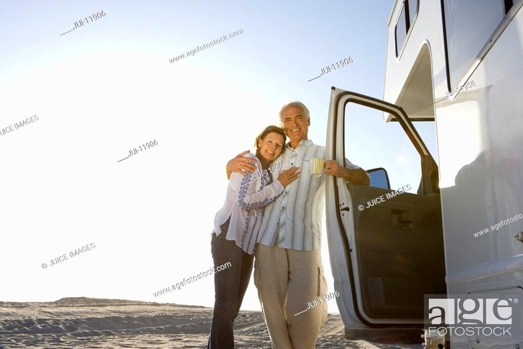 Stock Photo: Mature couple arm in arm by motor home on beach, smiling, portrait, low angle view sun flare.