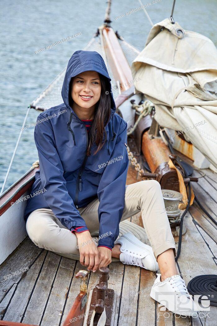 Imagen: Young woman with raincoat, Sailing boat, Pasaia port, Gipuzkoa, Basque Country, Spain, Europe.