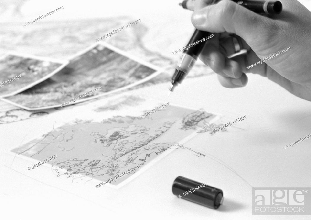 Stock Photo: Hand holding pens above drawing, close-up, b&w.