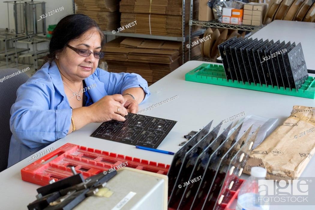 Stock Photo: Detroit, Michigan - A worker for A123 Systems assembles circuit board for unmanned aerial vehicles (drones) manufactured by Detroit Aircraft Corporation.