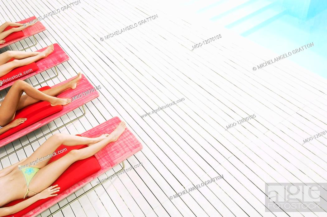 Stock Photo: Young Women Sunbathing by pool on deckchairs low section high angle view.
