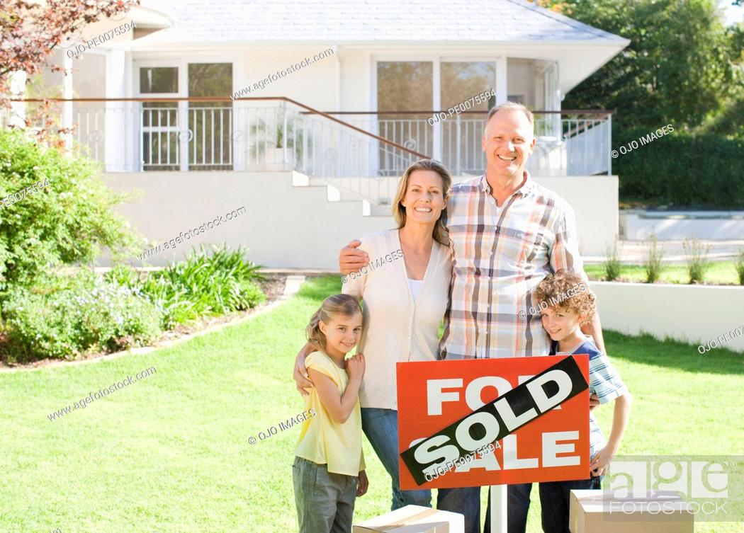 Stock Photo: Family standing with sold sign of their new house.